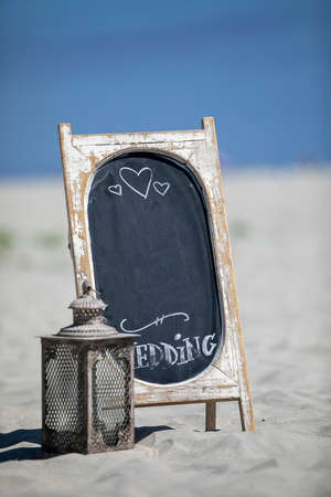 Lantern and chalkboard with a wedding message on a sandy beach