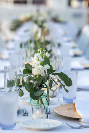 Long table with white linen them set for a wedding ceremony in an outdoor area