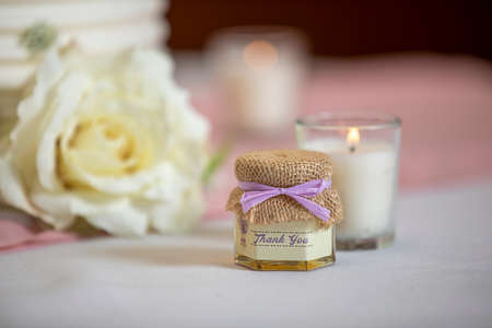 Handout gift and lit candle on a table at a wedding ceremony