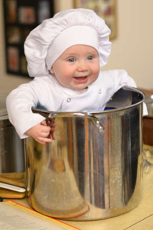 Baby with a chef hat sitting in a soup pot for a cute portrait