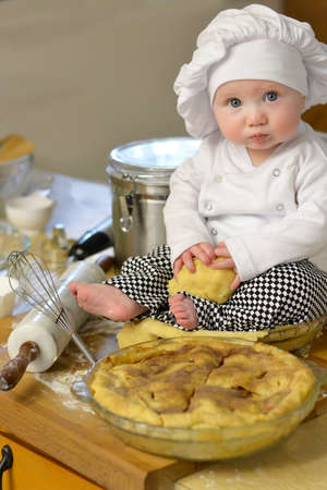Kitchen setting with a baby chef surrounded by baking ingredients to make a pie