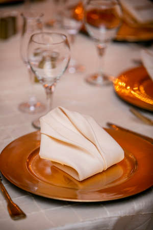 Traditional golden glass plate and table setting for a wedding ceremony dinner