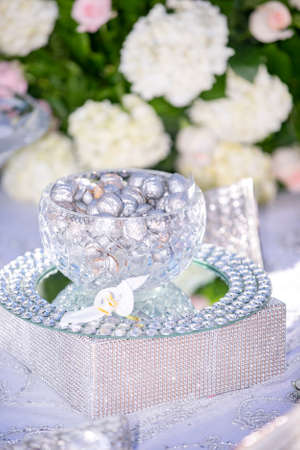 Wedding decor of silver coated walnuts and almonds in a glass bowl and tray with traditional Persian decor