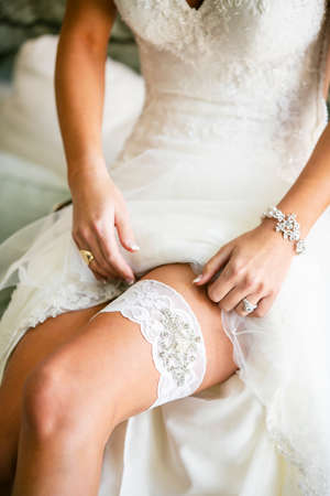 Bride getting ready for her wedding ceremony and putting on the bridal garter