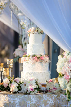 Table with a wedding cake decorated with white fondant icing and pink and white roses in an outdoor setting