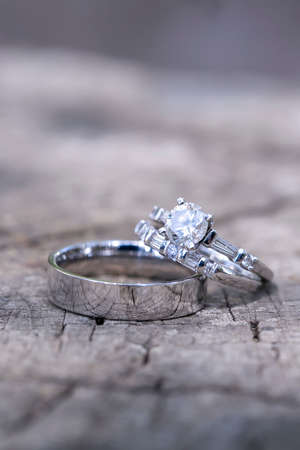 Traditional wedding band and diamond rings on a stone background