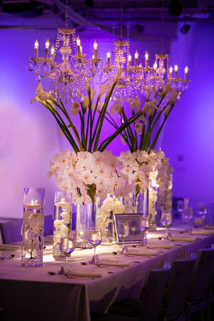 White flowers and decor for a wedding ceremony table setting and lit floating candles