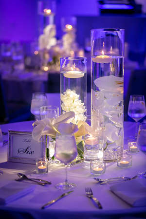 Blue lit ambiance wedding ceremony tables with lighted glass container and floating  candles
