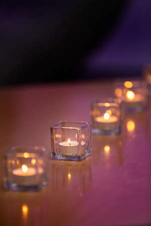 Lit tealight candles in glass containers on a glossy table top with a purple tint background