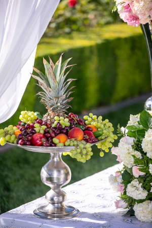 Outdoor weddinig decor and silver tray filled with grapes, cherries, pineapple, and various other fruit as a buffet