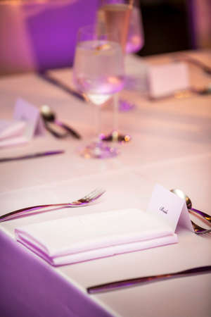Neatly elegant place setting with napkins and flatware and name tage for a wedding ceremony party