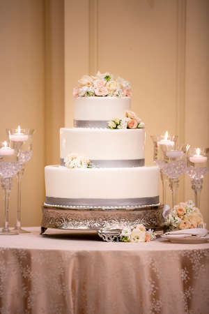 Wedding ceremony three tiered cake made with white frosting and grey trim decorated with white and pink roses on a table covered with silk tablecloth