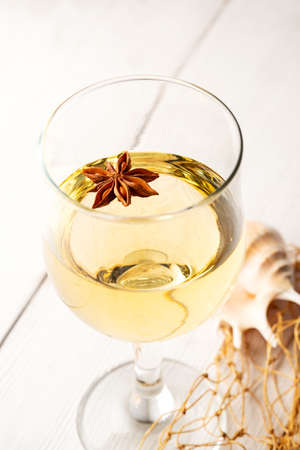 a glass of white wine over a white wooden background. marine theme