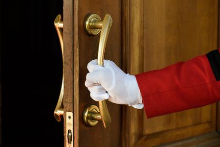 the doorman opens the hotel door hands in white gloves. welcome Stock fotó