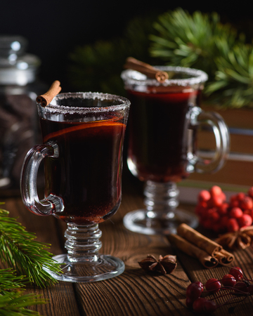 Mulled wine with spices and citrus fruit on wooden background 免版税图像
