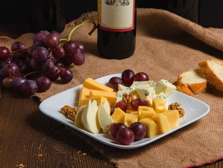 cheese and grapes on a plate on burlap with bread