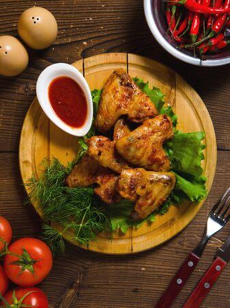 Fried chiken wings on wooden plate. dark table, top view Stock fotó