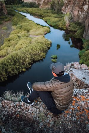 a guy sits on the edge of a cliff and admires the view at dawn