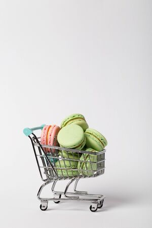 heap of color macaroons in a toy shopping cart on white background