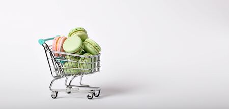 heap of color macaroons in a toy shopping cart on white background. banner format