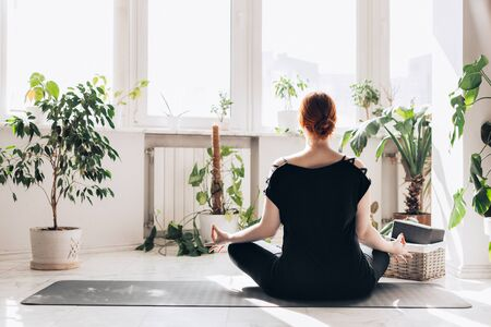 caucasian redhair woman practice yoga at home in a white light living room. window and plants background
