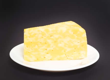 albumin: A large piece of cheese on a white plate on a dark background