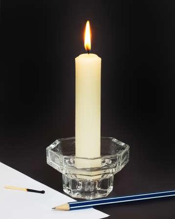 paraffine: Grote witte paraffine kaars, een potlood en een vel papier op een zwarte achtergrond.