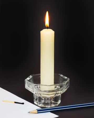 paraffin: Large white paraffin candle, a pencil and a sheet of paper on a black background. Stock Photo
