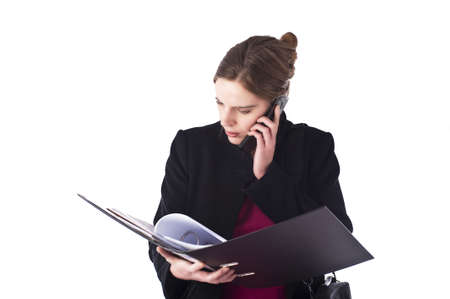 Business woman bearing files and using a cellular phone. Isolated, whiote background. Stock Photo