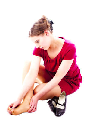 pretty young woman take off her shoes. White background. Stock Photo