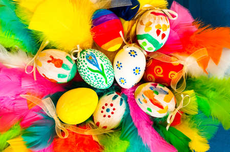Traditional arrangement of easter eggs and easter feathers photo