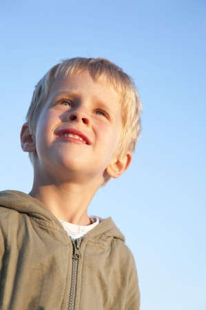 Portrait of a young boy, 3 years old, in the warm light of the evening sun