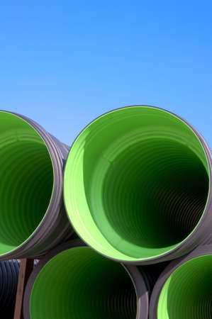 Stack of green tubes on a construction site Stock Photo