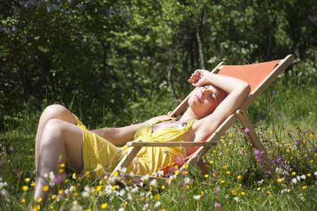 Young woman sitting in a deck chair on a meadow full with flowers. Stock Photo