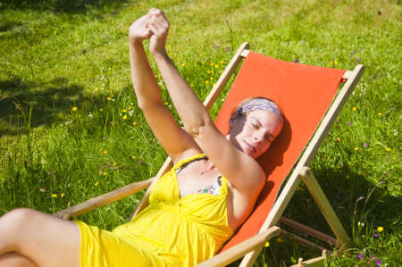 Woman relaxing in a deck chair i the sunlight.