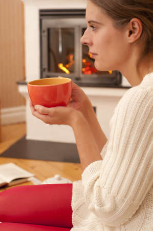Young woman sitting in front of a fireplace, with a cup of tea. Stock Photo