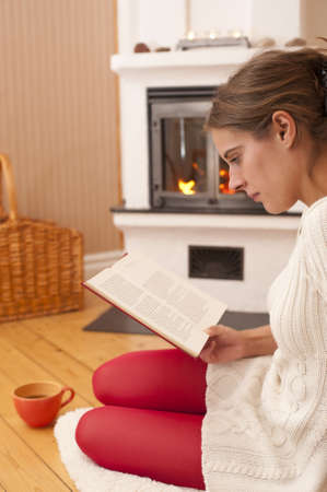 Young woman sitting in front of a fireplace, reading a book. Warm colors, looks like at home during a winter day.
