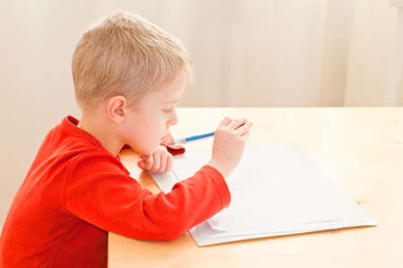 Cute little boy drawing a picture at home photo