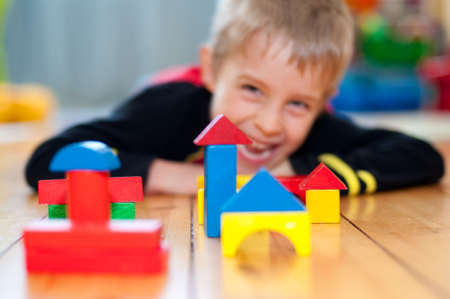 Happy boy playing with construction cubes, lying on the floor, looks into the camera. photo