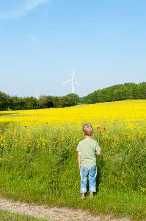 Preschool boy in front of a field of rape, looking forward to a wind turbine photo