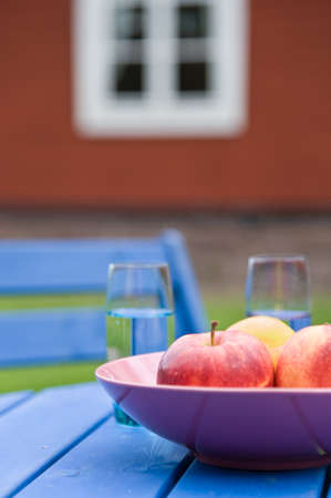 A bowl with apples and glases with water on a garden table