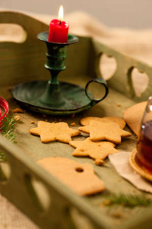 Lebkuchen und eine Tasse Tee auf einem Tablett zu Weihnachten begrenzten Schärfentiefe dekoriert, auf Lebkuchen konzentrieren