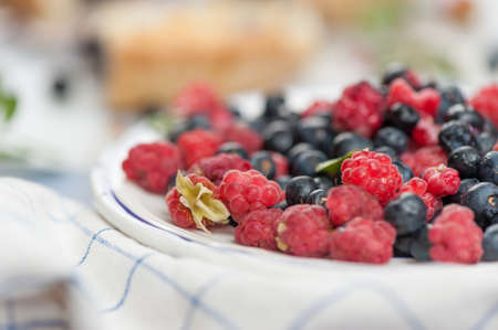Fresh wild blueberries and raspberries, in the background a cake