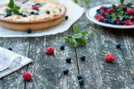 Fresh wild blueberries and raspberries and a blueberry cake Imagens