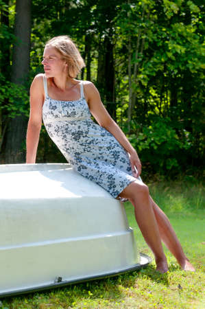 upturned: Attractive carefree barefoot woman in a summer dress reclining on an upturned boat hull in a lush garden enjoying the summer sunshine