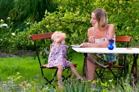 Mother and daughter sitting at a table in the garden enjoying a tasty snack which the little girl is eating watched by Mum Imagens