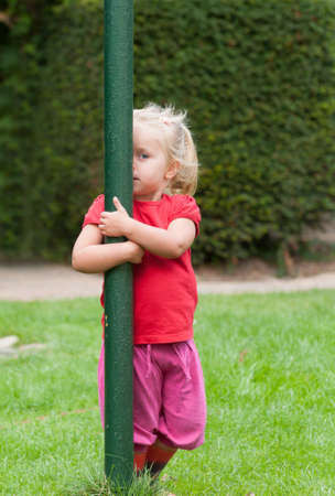 Little girl playing peek-a-boo in the garden peering out from behind a green pole that she is hugging with one eye