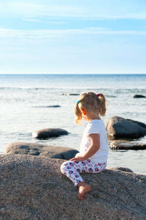 Rear view of a little girl straddling a boulder on the beach as she sits in the summer sunshine looking out to sea