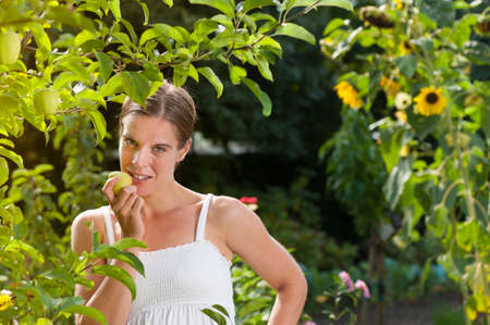 View through the foliage of an apple tree to an attractive woman eating a fresh healthy apple in her garden photo