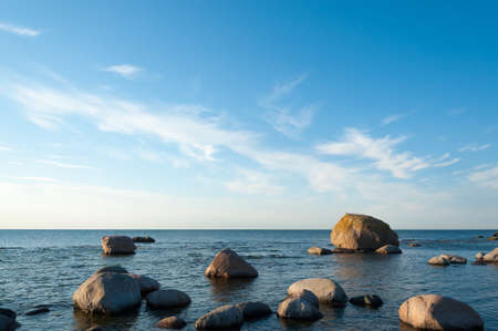 ebb: Low angle view of a rocky ocean coastal background with calm blue seas and light clouds in the sky